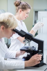 Photo of researcher conducting microscopic examination of sample